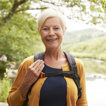Portrait Of Senior Woman Hiking Along Path By River In UK Lake District